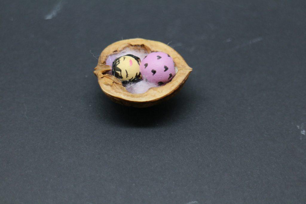 Figurine bébé fille cendre rose dans son berceau noix